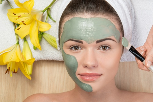 Close-up portrait of beautiful girl looking at the camera with a towel on her head applying facial clay mask and beauty treatments lying on a table in spa near yellow flower